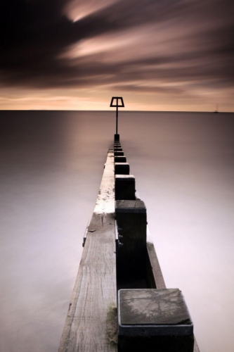 Wooden groyne looking out to sea with a metal rod at the end, very symettrical and moody.